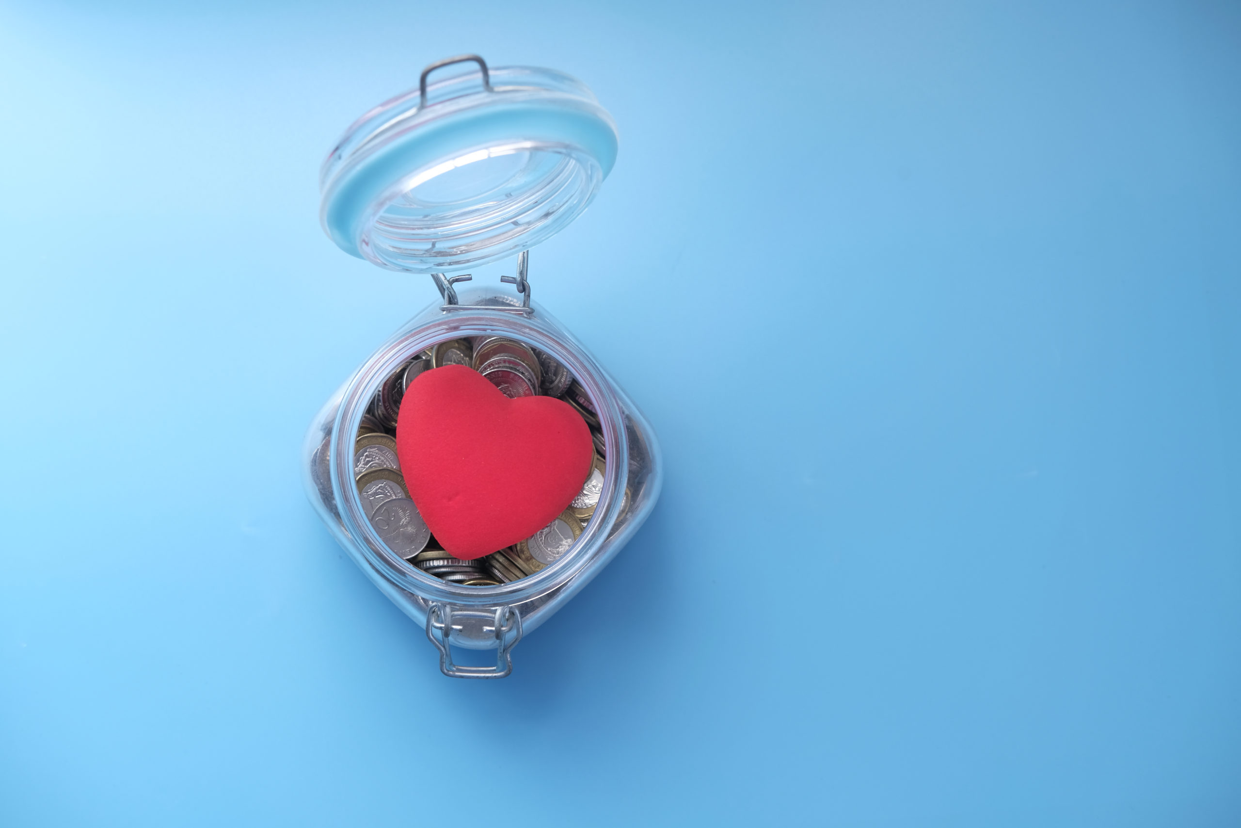 Red heart and coins in a jar on blue background